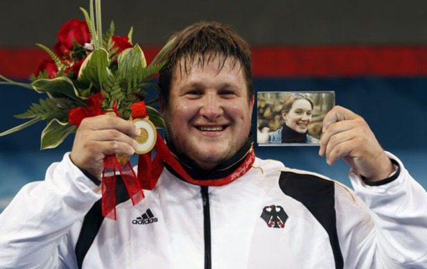 Matthias Steiner of Germany holds a photo of his late wife Susann as he poses with his gold medal in the men's +105kg Group A weightlifting competition at the Beijing 2008 Olympic Games August 19, 2008.     REUTERS/Alvin Chan (CHINA)